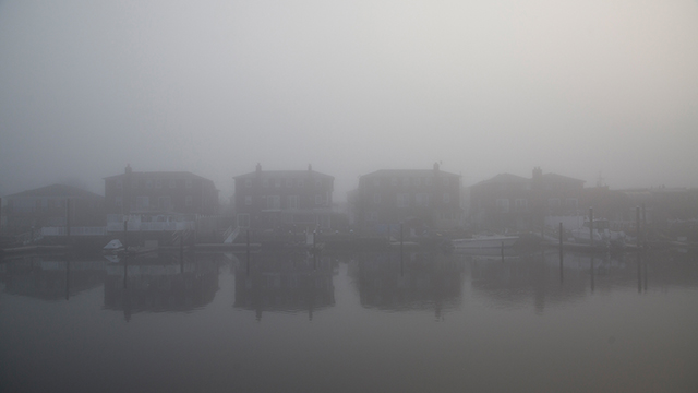 Houses obscured by thick fog.