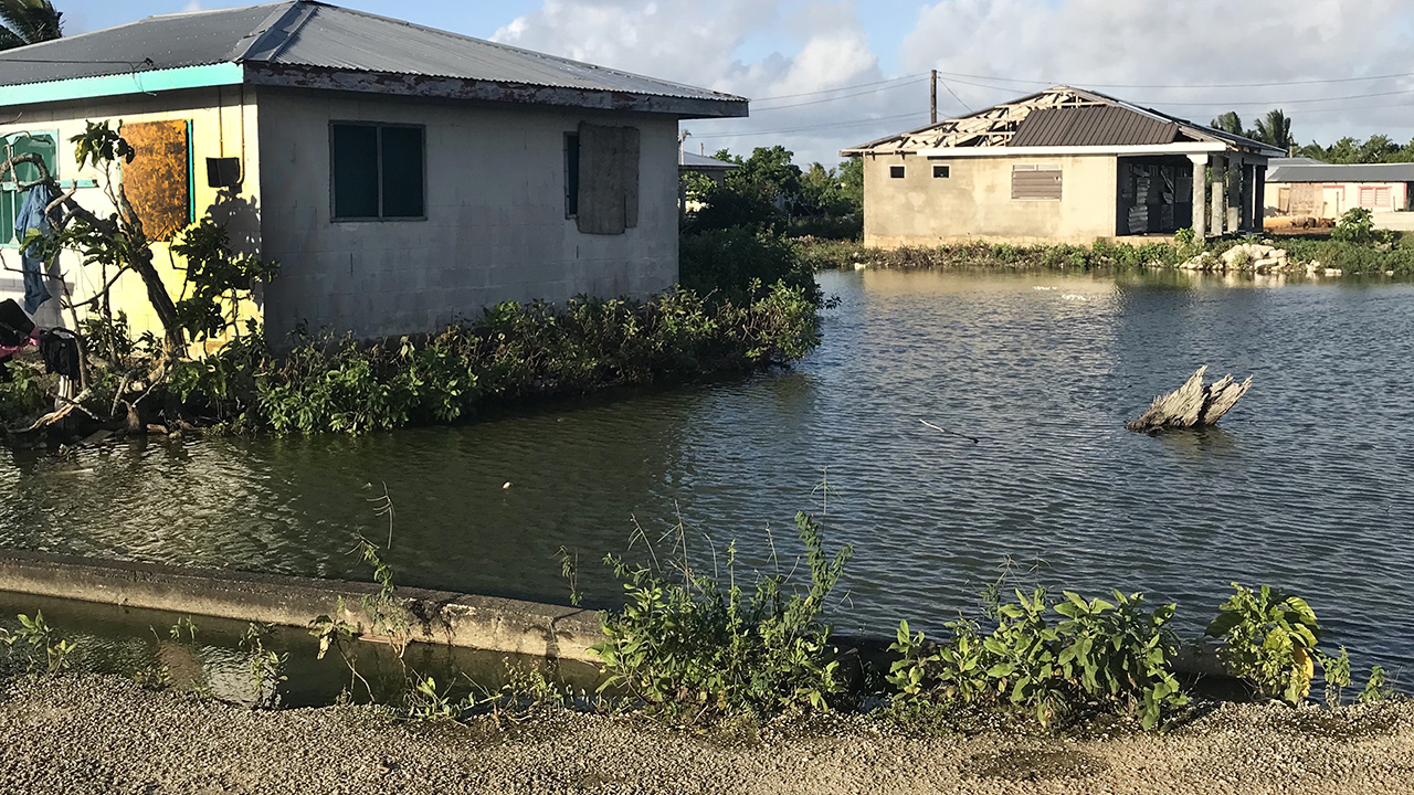 A flooded Tongan neighborhood with abandoned houses.